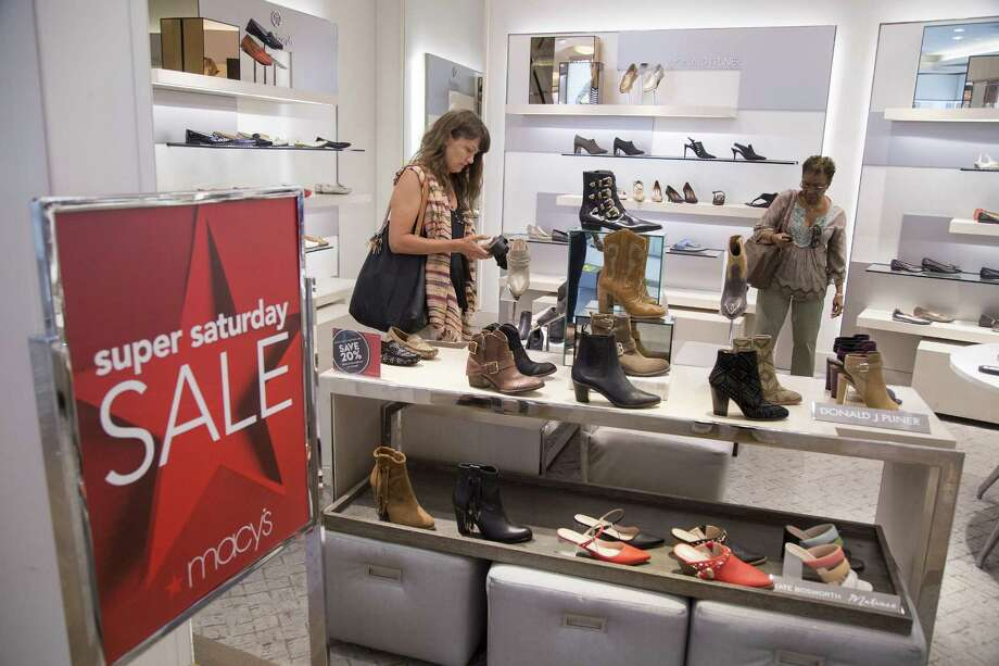 Shoppers look at shoes at a Macy's Inc. department store in New York. The Wall Street Journal reported that Macy's is in preliminary talks to be acquired by Hudson's Bay, a Canadian department store empire. Photo: Bloomberg News /File Photo / BLOOMBERG