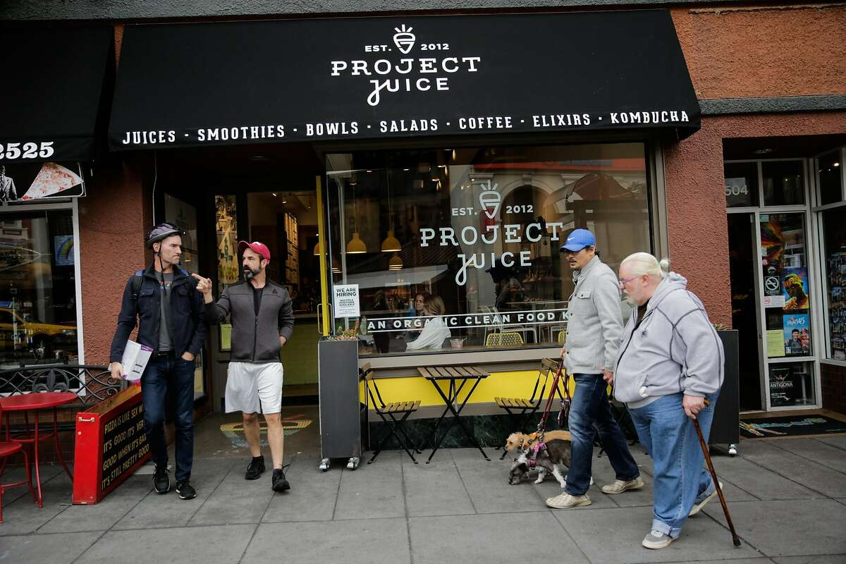 Friends Eric Knutson (left) and Joseph Hittinger (second from left) walk out of Project Juice after having smoothies together in San Francisco, California, on Thursday, Feb. 2, 2017.