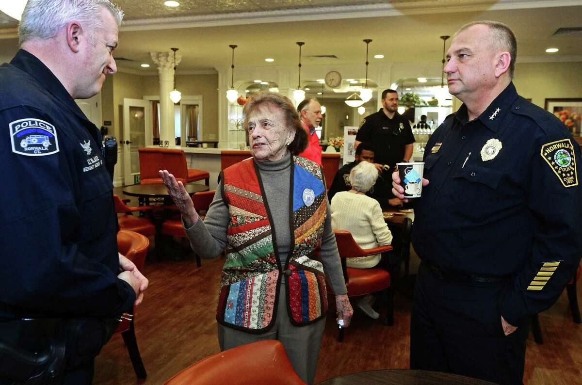 """Resident of Brightview senior housing, Virginia Place, welcomes Norwalk police Lt. Terry Blake and Chief Thomas Kulhawik during the weekly """"Coffee with a Cop"""" event in this file photo. Blake is featured prominently in a newly released video by the U.S. Attorney's Office features about community outreach initiatives in Norwalk."""
