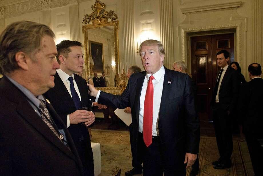 Trump advisor Steve Bannon, left, watches as President Donald Trump greets Elon Musk. Photo: BRENDAN SMIALOWSKI, AFP/Getty Images