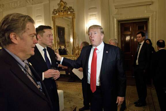 Trump advisor Steve Bannon (L) watches as US President Donald Trump greets Elon Musk, SpaceX and Tesla CEO, before a policy and strategy forum with executives in the State Dining Room of the White House February 3, 2017 in Washington, DC. / AFP PHOTO / Brendan SmialowskiBRENDAN SMIALOWSKI/AFP/Getty Images