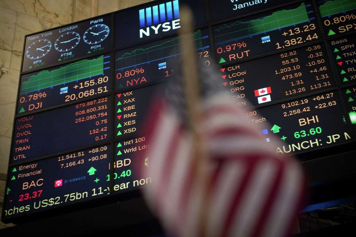 TOPSHOT - A video board shows the Dow Jones closing above 20,000 for the first time at the New York Stock Exchange January 25, 2017 in New York. The Dow Jones Industrial Average finished above 20,000 points for the first time Wednesday, after breaching the milestone at the open, extending a stocks rally that followed US President Donald Trump's election, which sparked hopes of pro-growth policies. / AFP PHOTO / Bryan R. SmithBRYAN R. SMITH/AFP/Getty Images