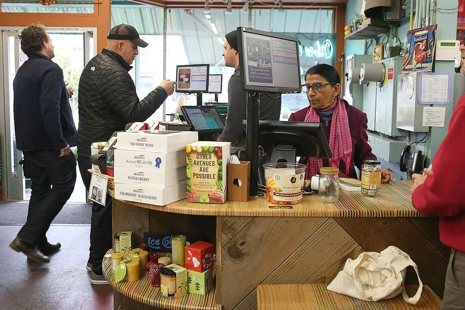 Shanta Nimbark Sacharoff (in pink scarf) works behind the counter at Other Avenues co-op in the Sunset District of S.F. Photo: Liz Hafalia, The Chronicle