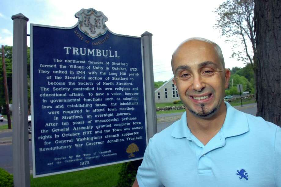Thomas Fantone poses in front of Trumbull's roadside history marker sign, at the intersection of White Plains Rd. and Unity Rd., in Trumbull, Conn. May 6th, 2010. Fantone has spent 15-years tracking down an photographing 168 of the 169 signs throughout the State of Connecticut. The last sign for his collection, Hartford, he hopes to photograph with Gov. Rell. Photo: Ned Gerard / Connecticut Post