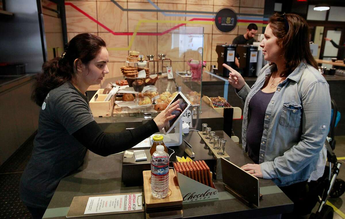 Nazira, (left) a refugee from Afghanistan takes an order from Sarah Gregson at 1951 Coffee Company in Berkeley, Ca., as seen on Friday Feb. 3, 2017. The 1951 Coffee Company trains Bay Area refugees as baristas to work in their newly opened cafe.