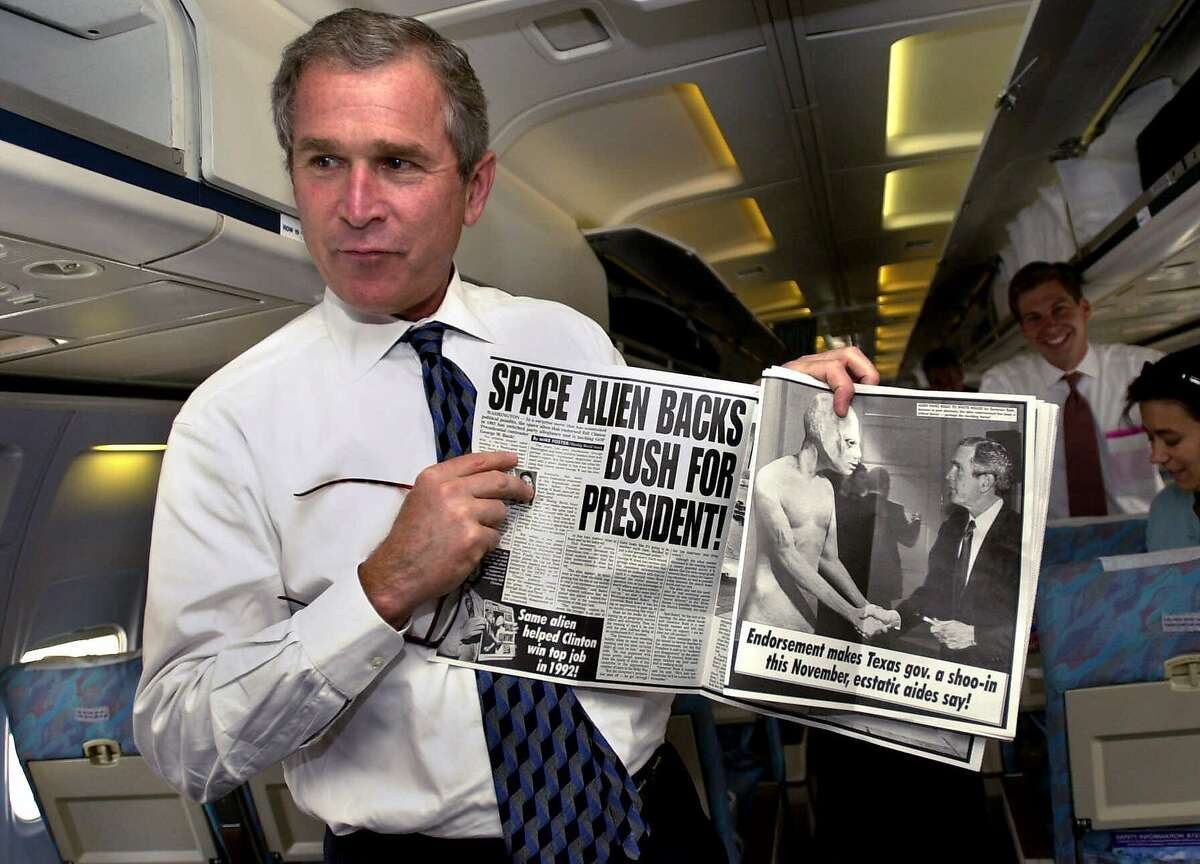 In this May 3, 2000 file photo, republican presidential candidate Texas Gov. George W. Bush displays a copy of the tabloid Weekly World News to reporters during a light moment aboard his campaign plane while leaving Austin, Texas. Weekly World News, the tabloid that for 28 years has chronicled sightings of Elvis, extraterrestrial activity and the exploits of Bat Boy, is no more. Its publisher said Tuesday, July 24, 2007 it would put out its last issue next month, maintaining only a Web presence. (AP Photo/Eric Draper, file)