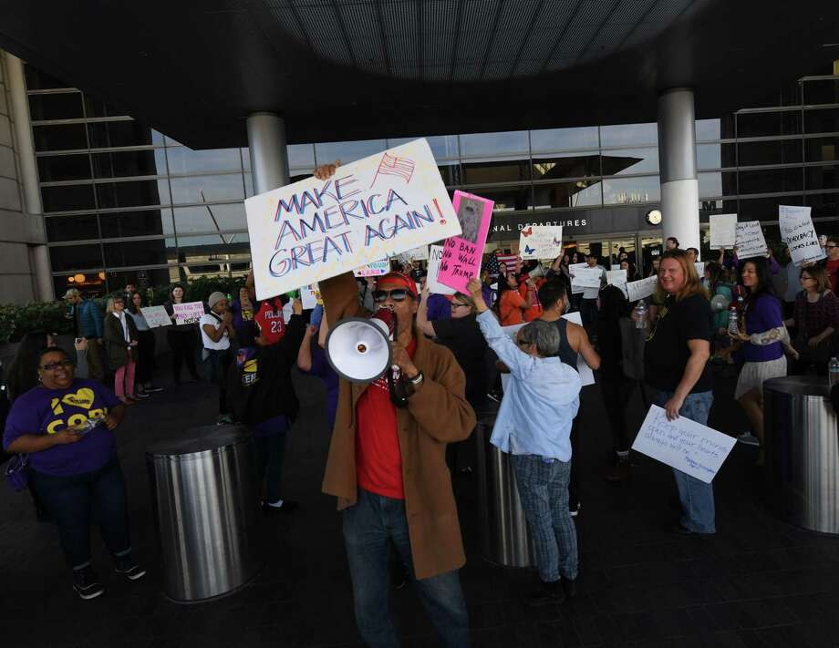 A pro-Trump supporter stands in front of a protest against the immigration ban at the Los Angeles International Airport, California on Jan. 30. Trump's executive order suspended the arrival of all refugees for at least 120 days, Syrian refugees indefinitely -- and bars citizens from Iran, Iraq, Libya, Somalia, Sudan, Syria and Yemen for 90 days. Photo: MARK RALSTON /AFP /Getty Images / AFP or licensors