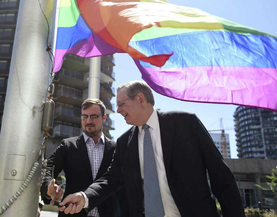 Executive Director of Triangle Community Center Anthony Crisci, left, and Stamford Mayor David R. Martin raise the LBGT rainbow-colored flag outside the Government Center in Stamford, Conn. Wednesday, June 15, 2016. Dozens gathered to honor the 49 victims gunned down at an Orlando gay nightclub early Sunday in the worst mass shooting in modern U.S. history. Photo: Tyler Sizemore / Hearst Connecticut Media / Greenwich Time