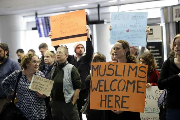 Protesters holds signs at San Francisco International Airport to denounce President Donald Trump's executive order that bars citizens of seven predominantly Muslim-majority countries from entering the U.S., Monday, Jan. 30, 2017, in San Francisco. (AP Photo/Marcio Jose Sanchez)