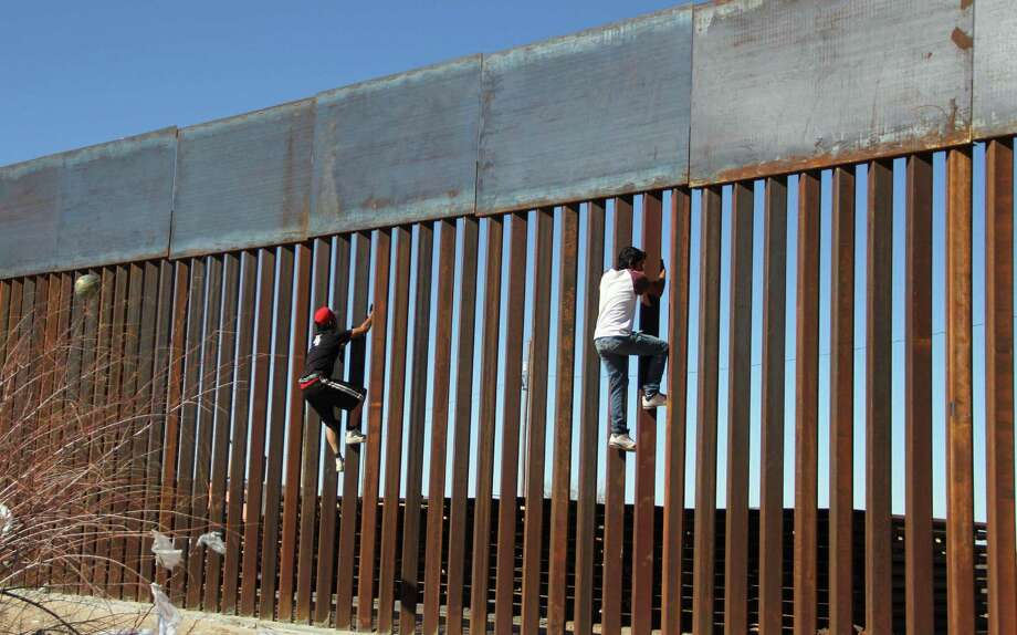 Mexican boys climb the barrier separating Ciudad Juarez from El Paso. Photo: Herika Martinez /AFP /Getty Images / AFP or licensors