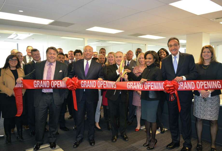 Former San Antonio Mayor Henry Cisneros (second from right) helps cut a ribbon Friday at the investment banking firm of Siebert Cisneros Shank & Co., which is expanding its Wall Street office. Photo: Courtesy / Courtesy