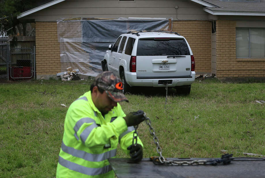 A tow truck driver prepares to remove a Chevy Tahoe Friday February 3, 2017 from the back yard of a home after crashing into a home on the 11,000 block of Janet Lee Drive. An officer at the scene said the driver was intoxicated and was not injured. The vehicle came to a halt after crashing through several fences and hitting the house. Photo: John Davenport, San Antonio Express-News / ©San Antonio Express-News/John Davenport