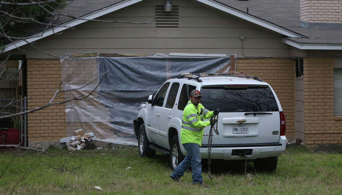 A tow truck driver prepares to remove a Chevy Tahoe Friday February 3, 2017 from the back yard of a home after crashing into a home on the 11,000 block of Janet Lee Drive. An officer at the scene said the driver was intoxicated and was not injured. The vehicle came to a halt after crashing through several fences and hitting the house.