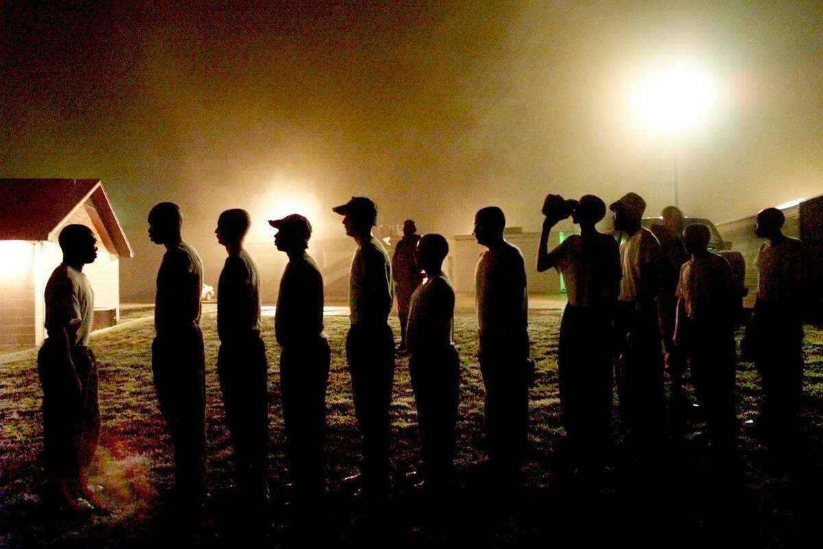 Juvenile offenders line up under the lights of the exercise yard at the Bill Logue Juvenile Justice Center Boot Camp in Waco at about 5:30 a.m. in 2001. Through light rain and fog, they scramble through an obstacle course and then wait their turn in line to run sprints. The Texas Legislature is looking at restructuring the entire juvenile justice system; critics say it needs major improvements.