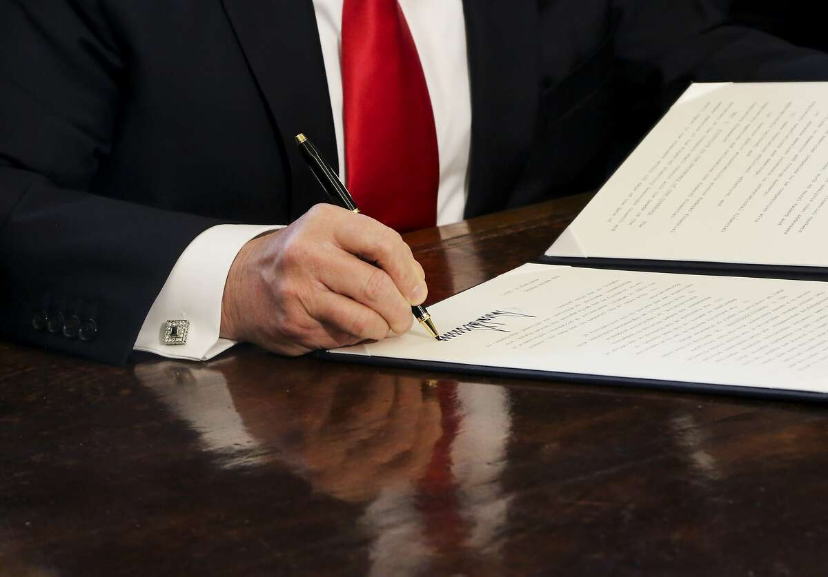 President Trump signs an executive Order in White House