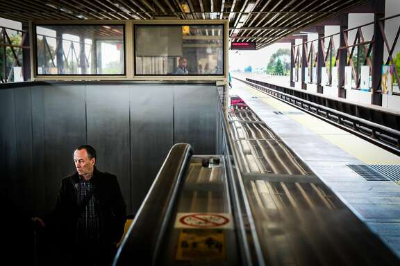 Jerry Gagnon (left) rides up the escalator at the Rockridge BART station in Oakland, California, on Thursday, June 9, 2016.