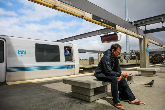 Brian Hurst (right) checks his phone while a BART conductor   looks to make sure all passengers have boarded the train, at the Daly City BART station, in Daly City, California, on Monday, April 11, 2016.