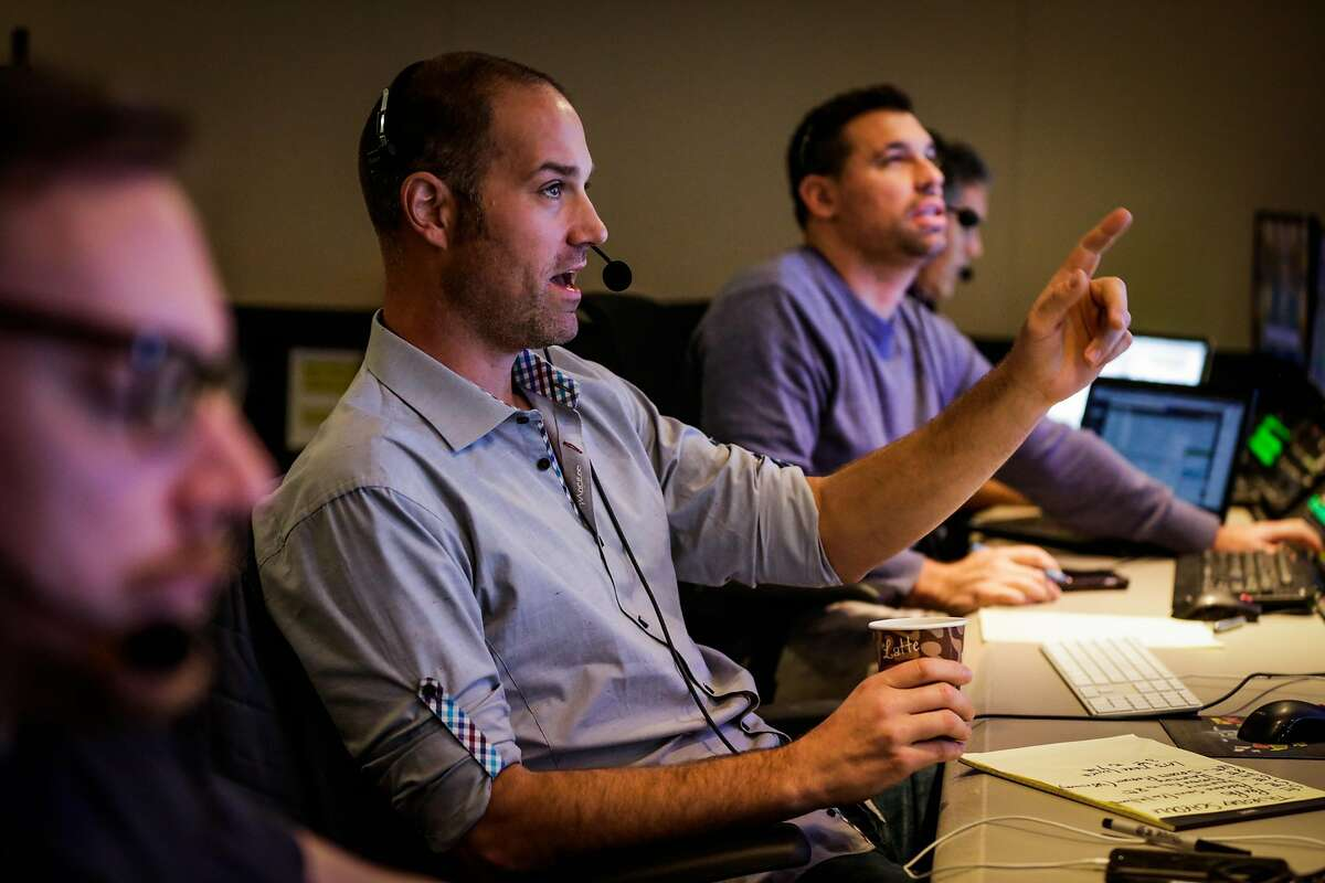 Ross Miller (center) does a countdown while speaking into his headpiece as he works in the control room at Pac-12 Networks in San Francisco, Calif., on Thursday January 12, 2017.