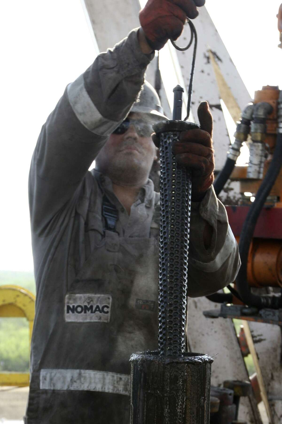 METRO -- Floorhand, Draden Copepland, cleans a filter on a drilling rig at a site near Carriso Springs on a well owned by Chesapeake Energy, Thursday, April 5, 2012. Jerry Lara/San Antonio Express-News