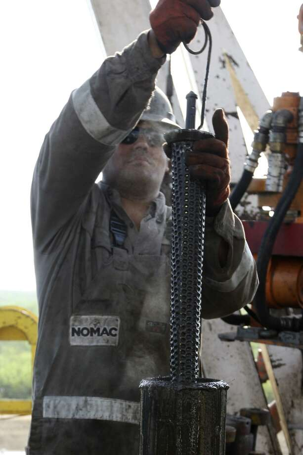 METRO -- Floorhand, Draden Copepland, cleans a filter on a drilling rig at a site near Carriso Springs on a well owned by Chesapeake Energy, Thursday, April 5, 2012. Jerry Lara/San Antonio Express-News Photo: Jerry Lara / San Antonio Express-News / © San Antonio Express-News