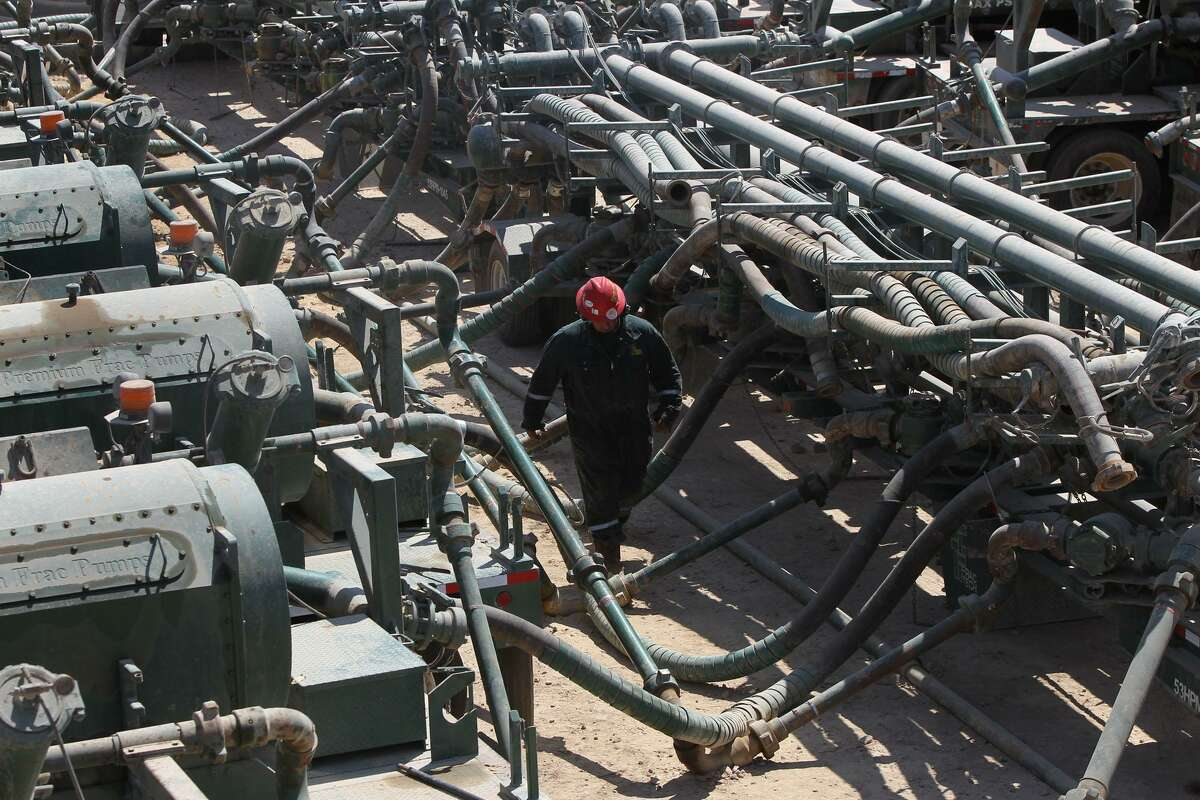 A worker walks near hydraulic fracturing pumps (left) at a Chesapeake Energy operation near Carrizo Springs in 2011. The number of South Texans who have sued Chesapeake over royalty payments has more than doubled since September.