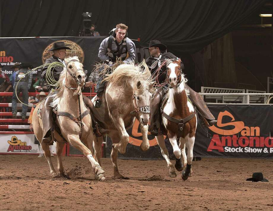 Pickup men Gary Rempel, left and Chase Cervi, right, close in to help a bareback bronc rider to safety at the 2016 San Antonio Rodeo. Photo by Greg Westfall. Photo: Courtesy Photo / Westfall PHOTO    2016