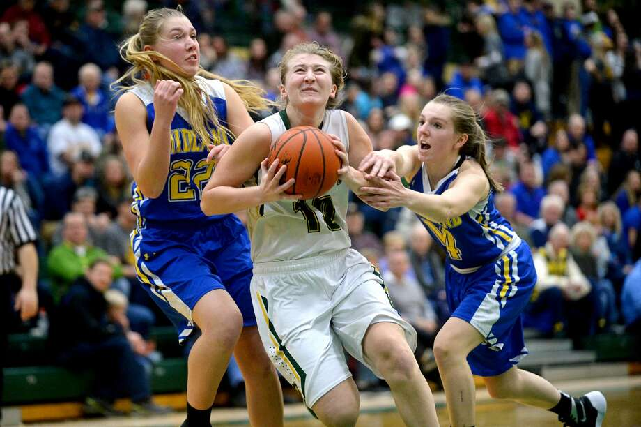 FILE — Dow's Ellie Taylor, center, goes for a layup while Midland's Jeni Grinwis, left, and Alex VanSumeren, right, try to stop her on Friday at H. H. Dow High School. Photo: Erin Kirkland/Midland Daily News