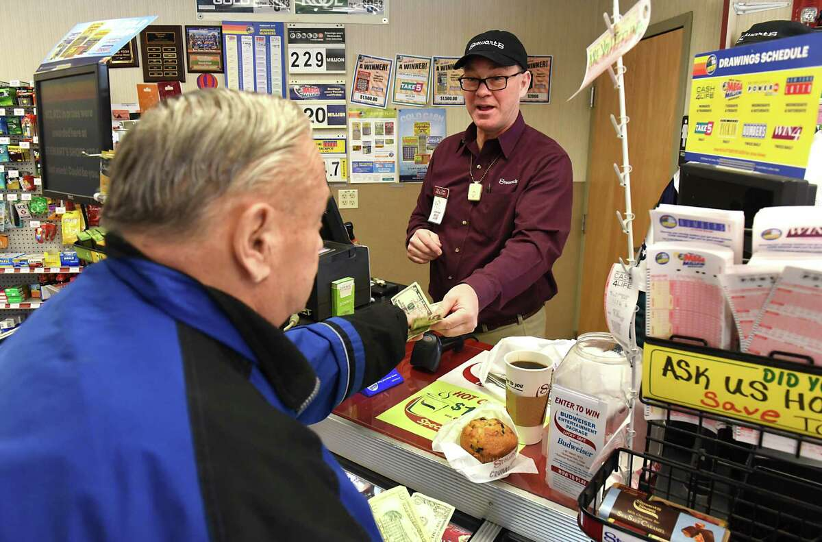 StewartOs Shops President Gary Dake, right, collects money from customer Denny Galka of Colonie as Dake continues a Holiday Match tradition by working a shift at the StewartOs Shop on Sand Creek Road on Friday, Feb. 3 2017 in Colonie, N.Y. Galka is a regular customer who comes in everyday and sometimes three times a day. The 2016 Holiday Match campaign received donations of more than $926,000 which becomes more than $1.85 million with the StewartOs match. (Lori Van Buren / Times Union)