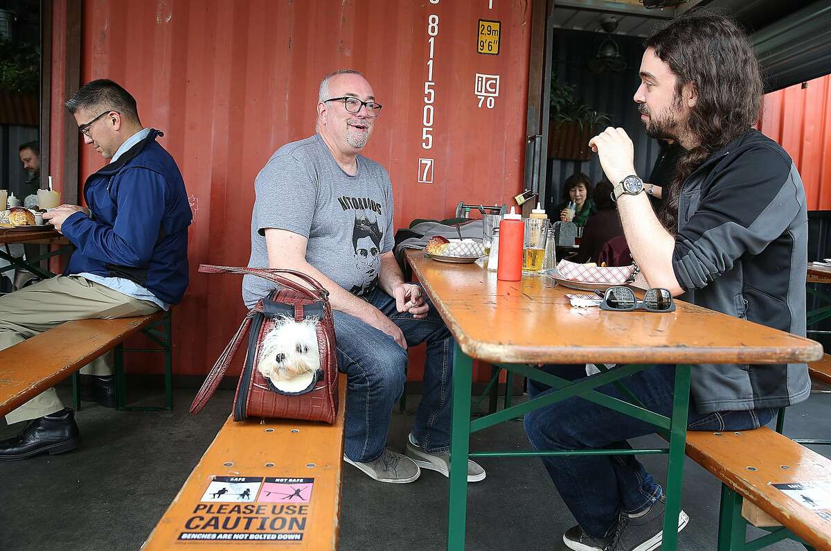 Ty (maltese middle) waits in his carrier while Jim Lynch, and Gregory Kasbarian have lunch at 4505 Burgers & BBQ outside on Friday, February 4, 2017, in San Francisco, Calif.
