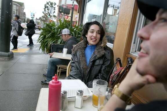 Nicole Preston (middle) enjoys a cheeseburger and beer with her friend Jonathan Palacioz (right) on Divisadero at Hayes streets on Friday, February 4, 2017, in San Francisco, Calif.