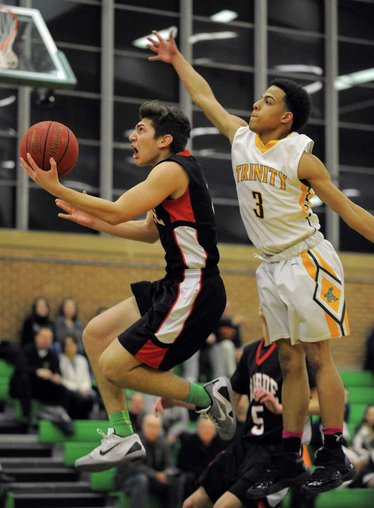 Warde Antonio Brancatoputs up a shot against Trinity Cameron Blake during a boys basketball game at Trinity Catholic High Schools Walsh Court in Stamford on Feb. 3, 2017. Warde defeated Trinity 67-60.