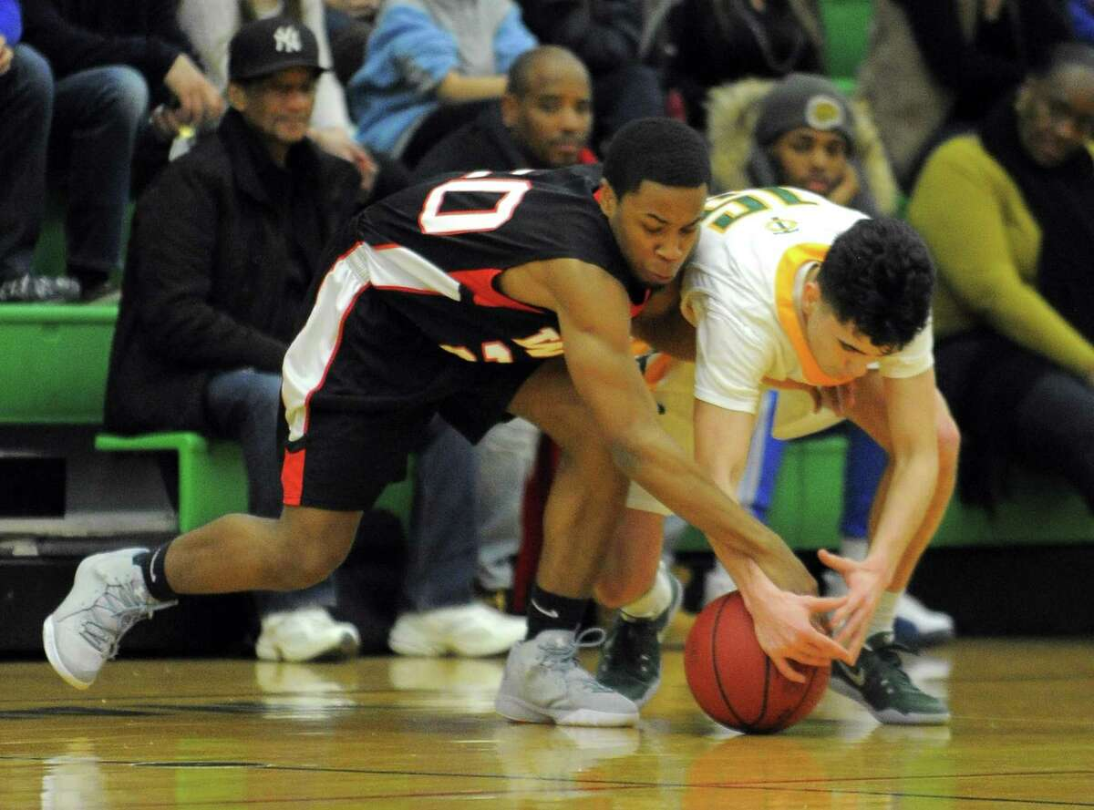 Warde Rashad Butler and Trinity Peter Galgano battle for a loose ball during a boys basketball game at Trinity Catholic High Schools Walsh Court in Stamford on Feb. 3, 2017. Warde defeated Trinity 67-60.