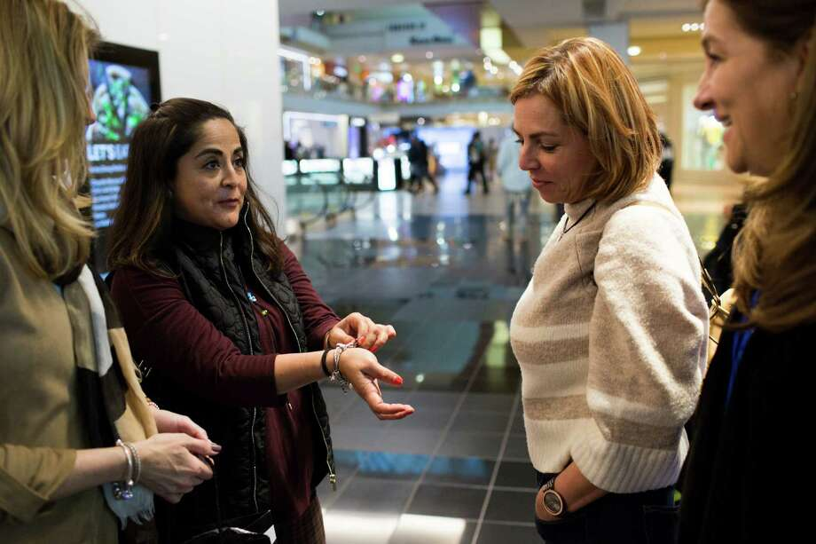 Lilliana Canseco shows her friends the collectible charm she bought for her bracelet during a trip to Houston Galleria, Friday, Feb. 3, 2017. ( Marie D. De Jesus / Houston Chronicle ) Photo: Marie D. De Jesus, Staff / © 2017 Houston Chronicle
