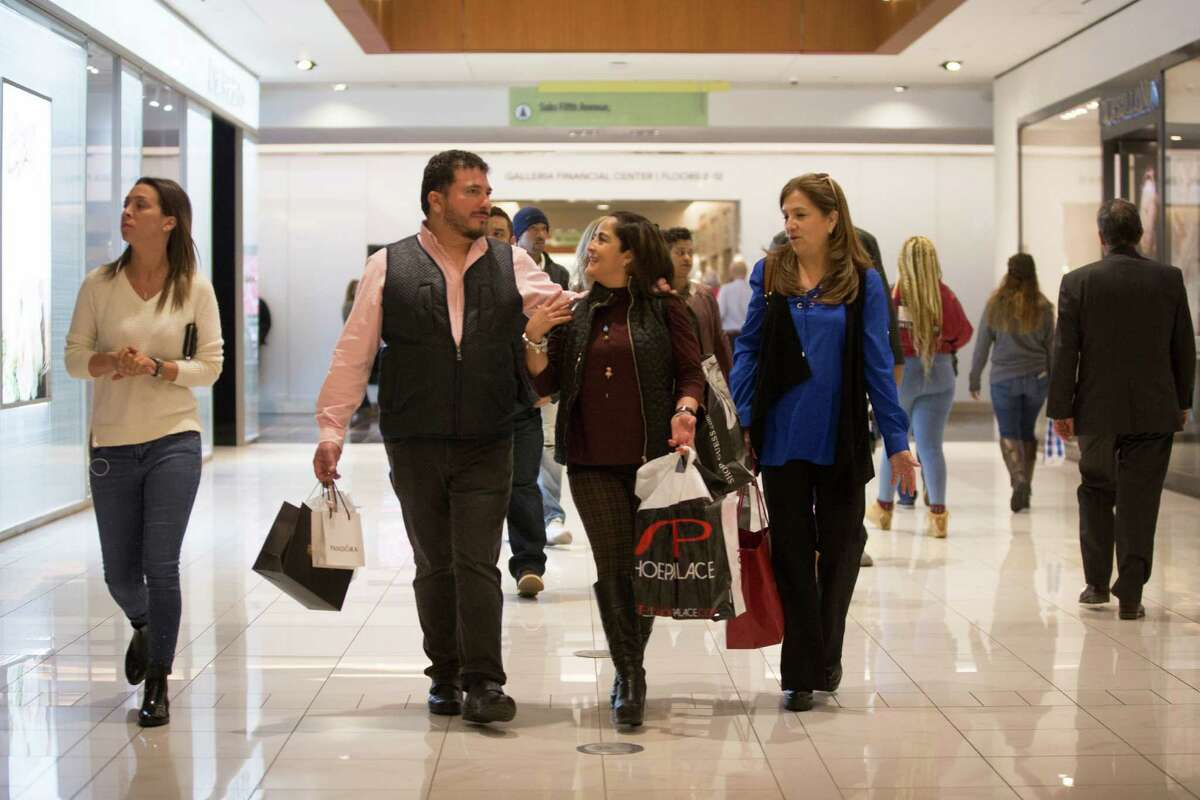 Sergio Vázquez, Liliana Canseco, center, and Ana Reyes walk through the Galleria on Friday. Vázquez said many Mexicans are cutting U.S. ties after the presidential election.