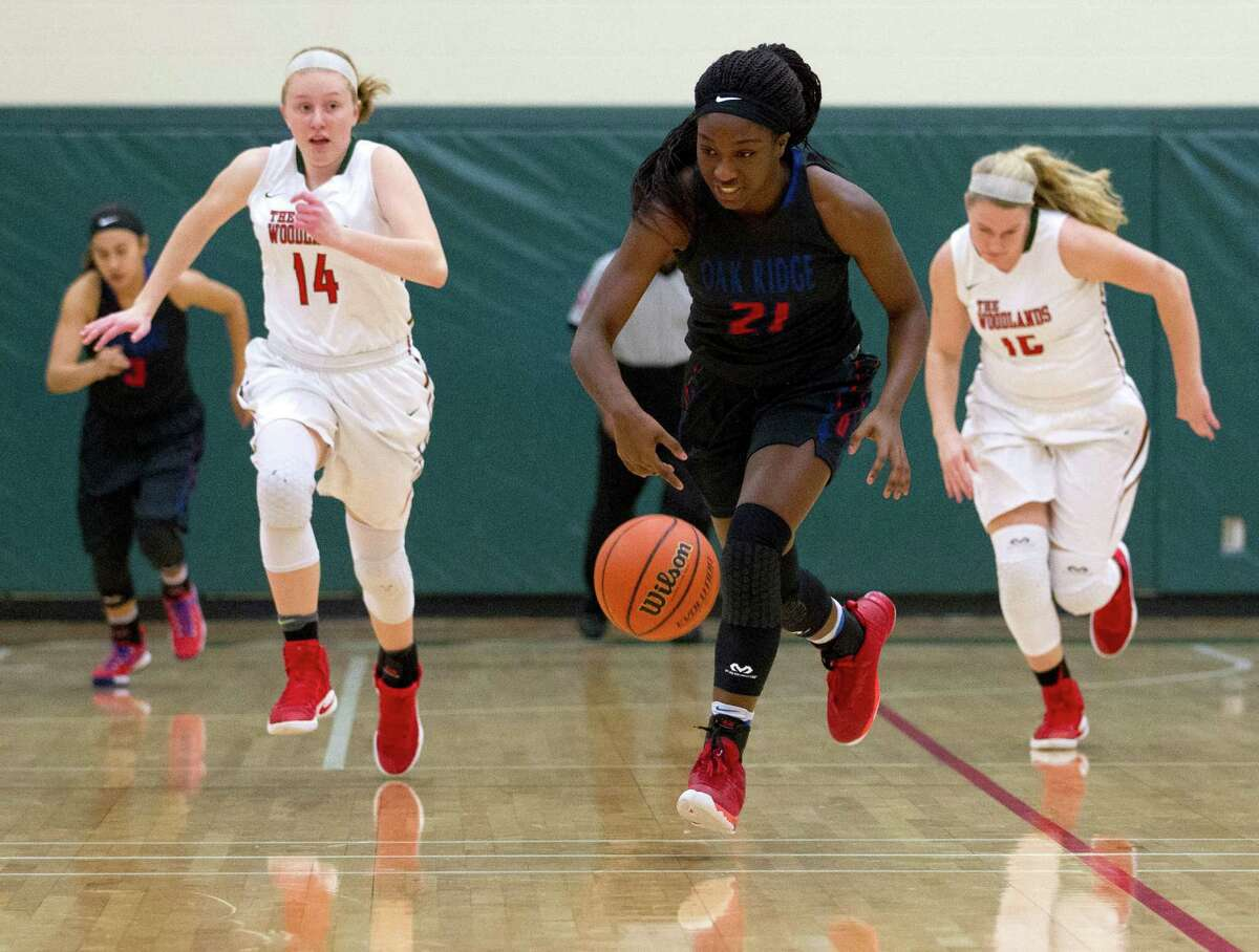 Oak Ridge small forward Alecia White (21) regains control of the ball after stealing it from The Woodlands guard Sarah Butterfield (12) during the second quarter of a District 12-6A high school girls basketball game at The Woodlands High School Friday, Feb. 3, 2017, in The Woodlands. Oak Ridge defeated The Woodlands 57-47.