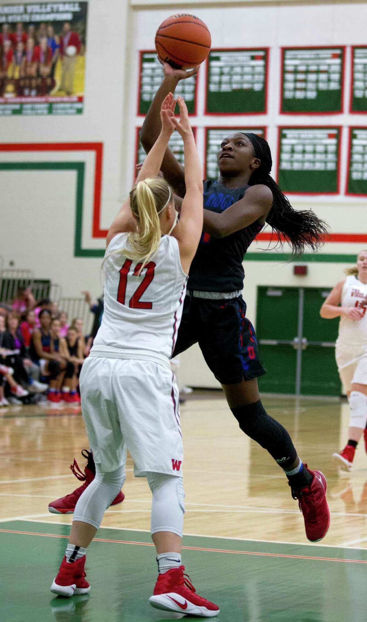 Oak Ridge small forward Alecia White (21) shoots over The Woodlands guard Sarah Butterfield (12) during the second quarter of a District 12-6A high school girls basketball game at The Woodlands High School Friday, Feb. 3, 2017, in The Woodlands. Oak Ridge defeated The Woodlands 57-47.