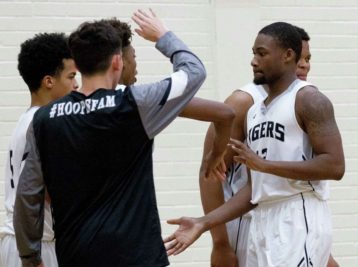 Quentin Brown slaps hands with his teammates during overtime of a District 12-6A high school boys basketball game at Conroe High School Friday, Feb. 3, 2017, in Conroe. Conroe defeated Lufkin 68-62 in overtime.