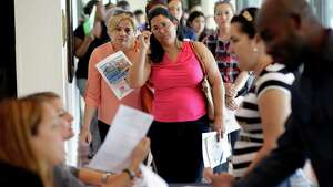 FILE - In this Tuesday, July 19, 2016, file photo, Reina Borges, left, stands in line to apply for a job with Aldi at a job fair in Miami Lakes, Fla. On Friday, Feb. 3, 2017, the Labor Department issues its jobs report for January. (AP Photo/Lynne Sladky, File)
