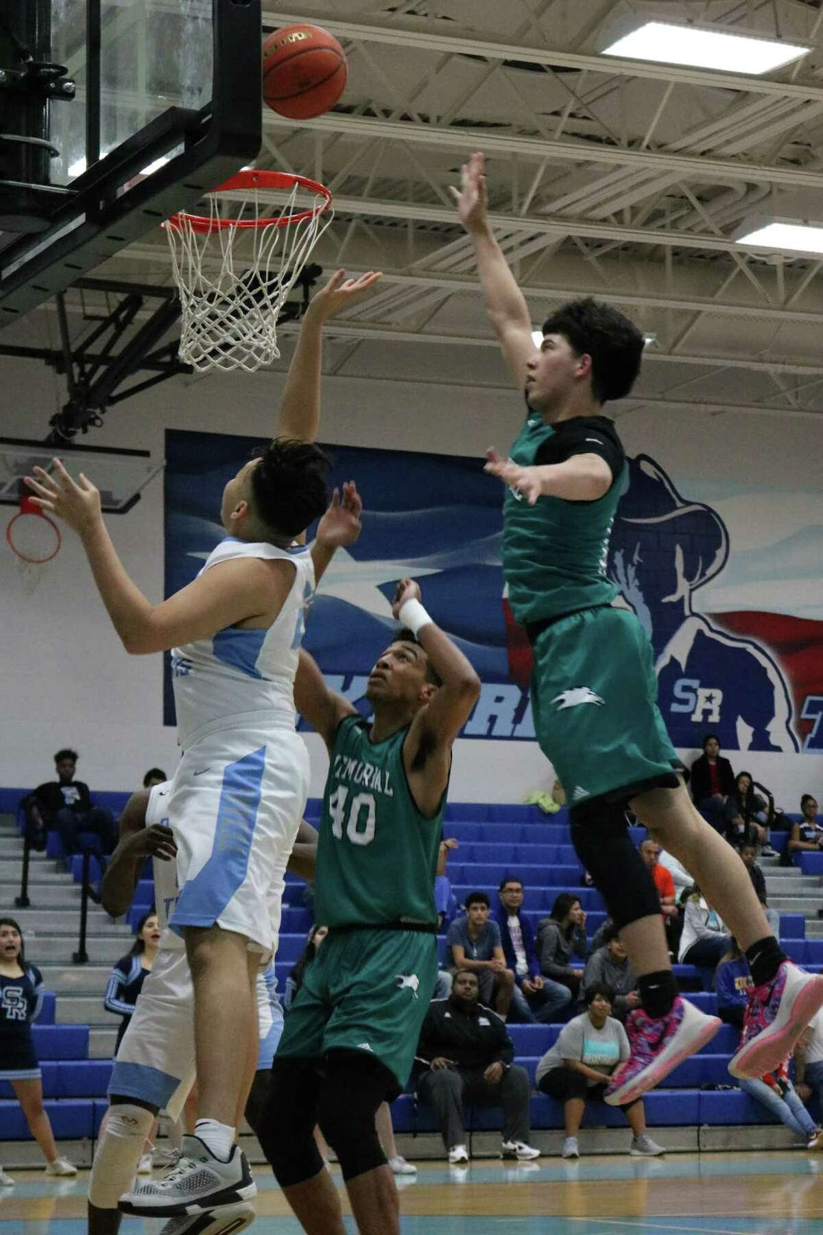 Sam Rayburn's Jeremy Mancia works his way past a pair of Memorial defenders in trying to score a first-half bucket.