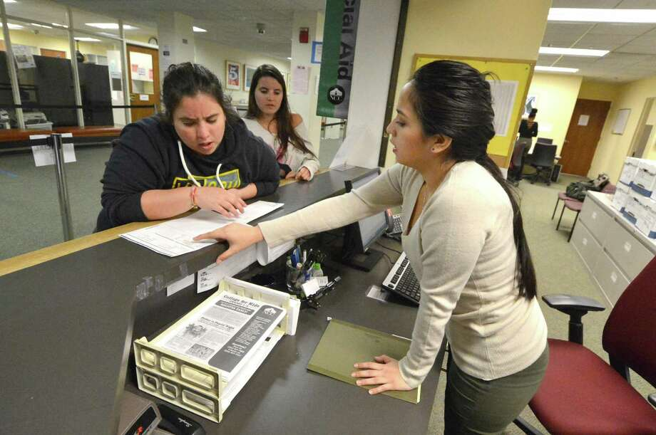 Genesis Mosquera, a work study student at Norwalk Community College helps student Stefanny Torero with a question at the Financial Aid office on Monday January 30, 2017 in Norwalk Conn. Photo: Alex Von Kleydorff / Hearst Connecticut Media / Connecticut Post