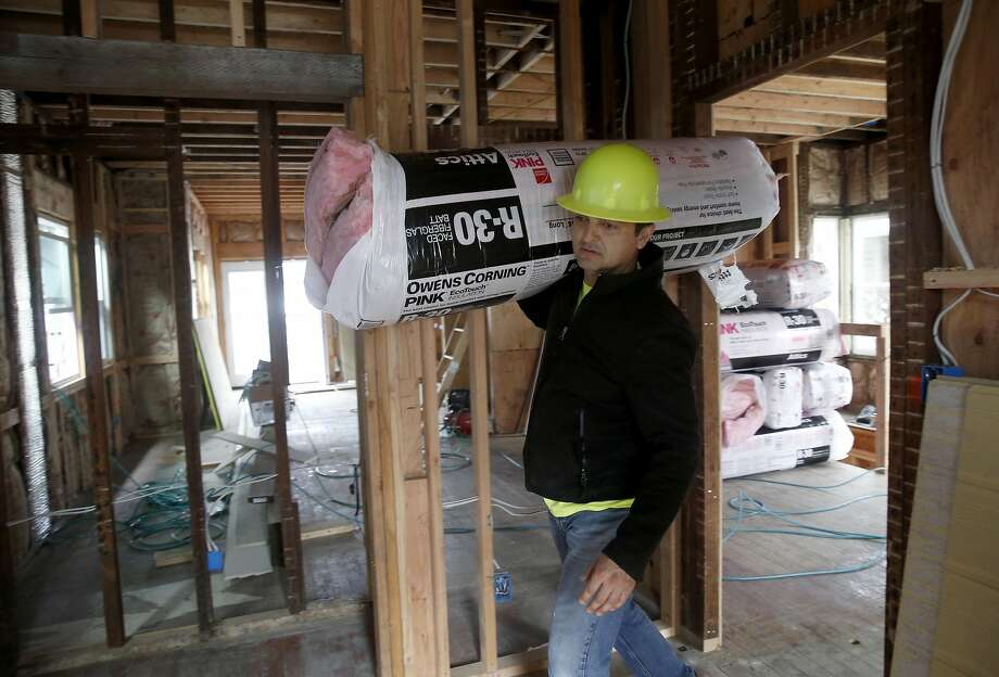 Juan Diaz, who grew up in East Oakland, carries construction material inside a redevelopment project on 65th Street in West Oakland. Photo: Paul Chinn, The Chronicle