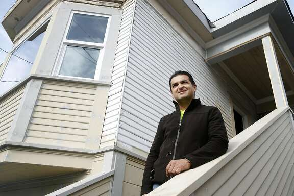 Juan Diaz is seen on the steps of a home redevelopment project on 65th Street in Oakland, Calif. on Thursday, Feb. 2, 2017. Diaz is the American-born son of Mexican immigrants who has established a successful career as a real estate investor.