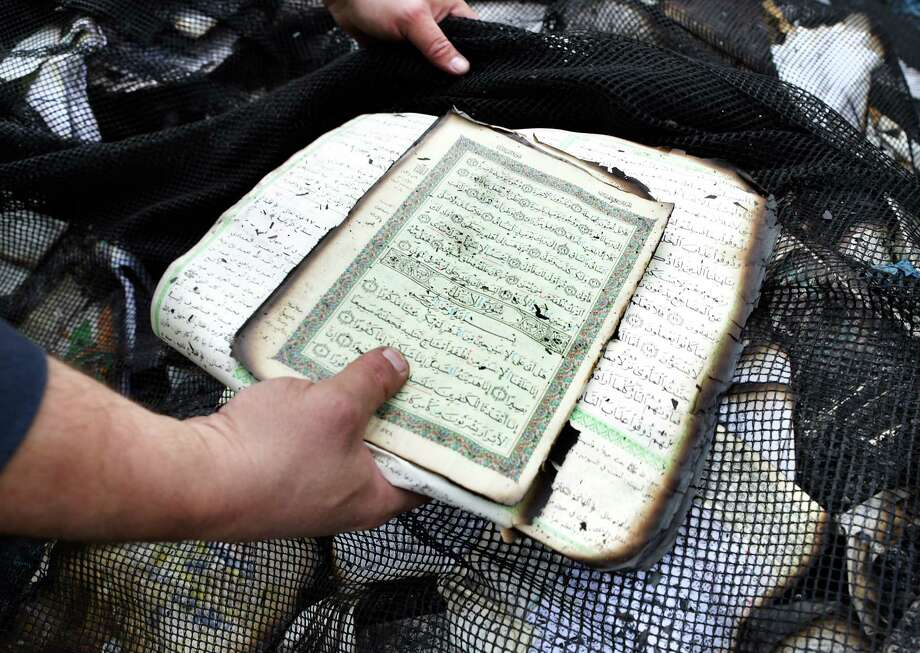 Imam Osama Hassan places pages from a Quran with others he has found after the total loss of the Victoria Islamic Center, in Victoria, Texas on Tuesday, Feb. 2, 2017. Photo: Bob Owen, San Antonio Express-News / ©2017 San Antonio Express-News
