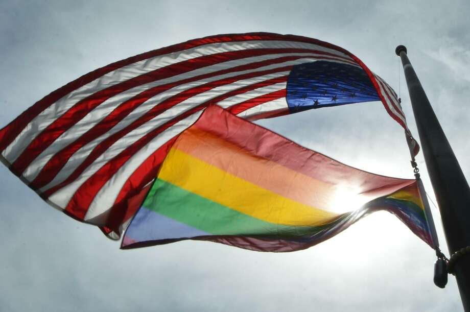 The American flag and the rainbow flag fly at half staff over St. Paul's on the Green Church on Monday, June 13 in Norwalk. On Tuesday, Feb. 7 from 7-8:30 p.m., St. Paul's will host a discussion with Imam Daaiyee Abdullah, the first openly gay imam in the United States and one of three openly gay imams in the world. Photo: Alex Von Kleydorff / Hearst Connecticut Media
