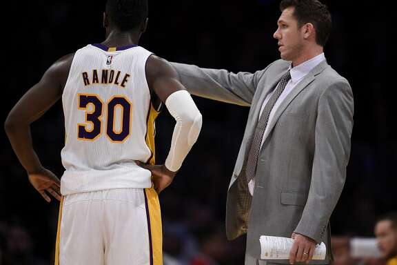 Los Angeles Lakers head coach Luke Walton, right, talks with forward Julius Randle during the first half of an NBA basketball game against the Toronto Raptors in Los Angeles, Sunday, Jan. 1, 2017. (AP Photo/Kelvin Kuo)