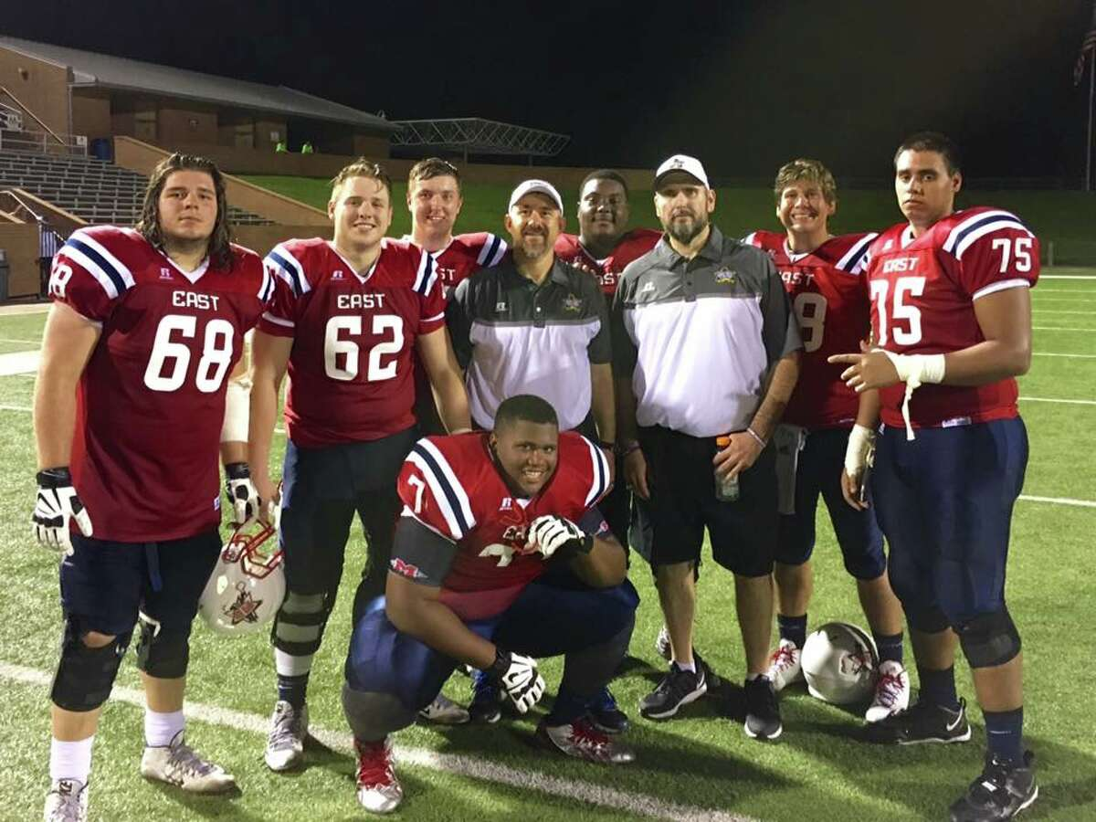 Coaches Mike Troutman (center left) and Jim Scott (center right) pose with the 2016 Bayou Bowl offensive line. Troutman, the o-line coach for the Houston high school all-star game, insisted that his players meet Scott, whom he considers an inspiration, both professionally and personally. Troutman said that involving Scott was impactful, and helped him know he was not forgotten.