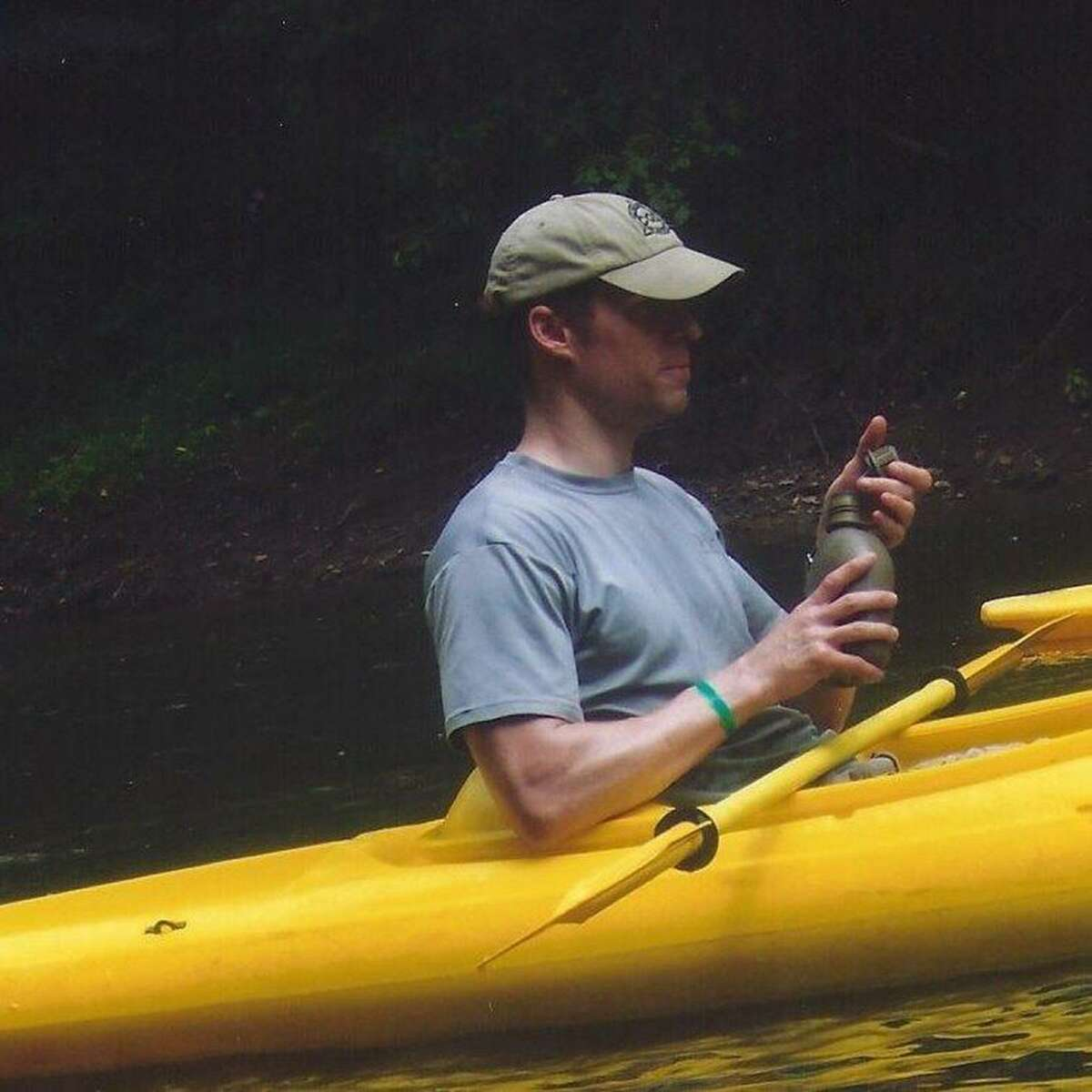 """Steven Bellino cradles a canteen while canoeing in this undated photo. Always in good physical condition, he posted top scores on his PT tests, but his last attorney, Dan Conway, told the family he struggled at Lackland. ?""""Steve started having problems with the Air Force from almost the time that he got down there,?"""" Conway said in a recorded conversation. Photo courtesy of Scott Workman"""