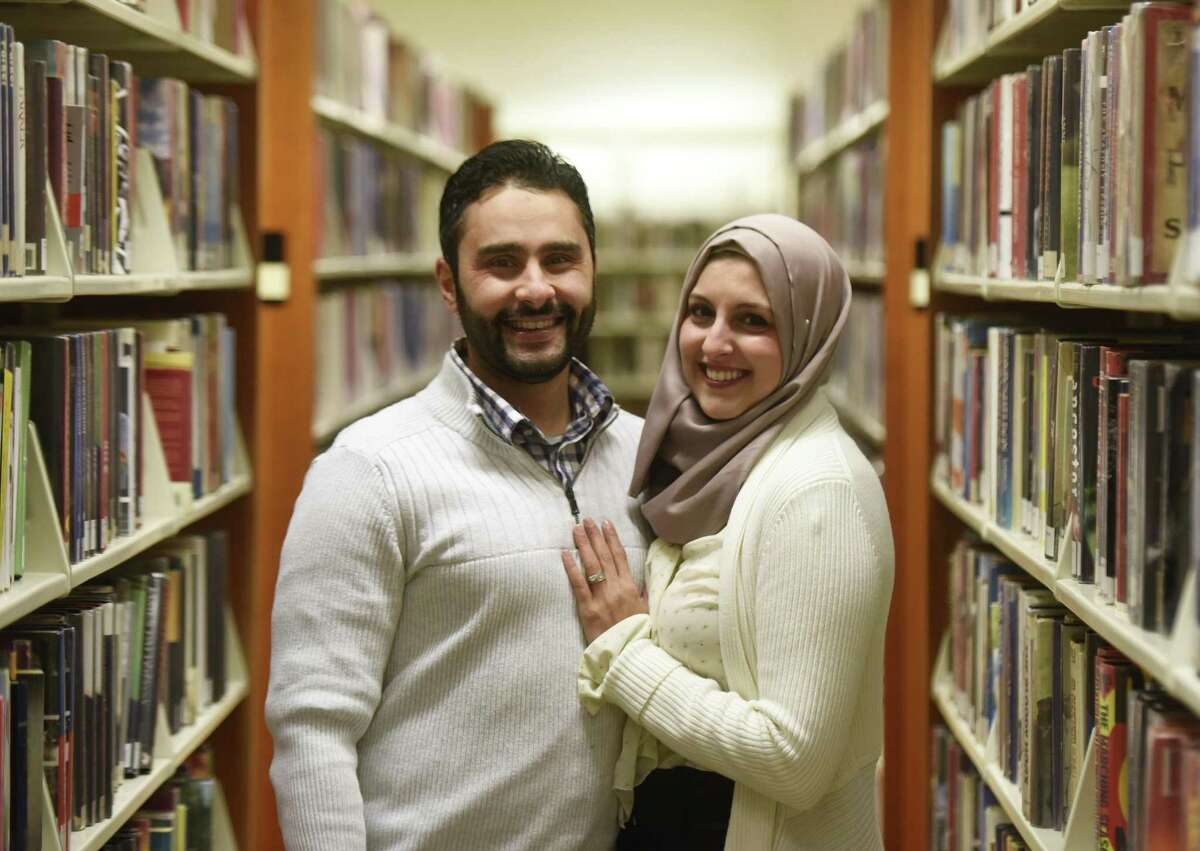 Stamford residents Shaimah Hamdan and her husband Fadi El-Ghussein pose inside the Ferguson Library near their home in downtown Stamford.