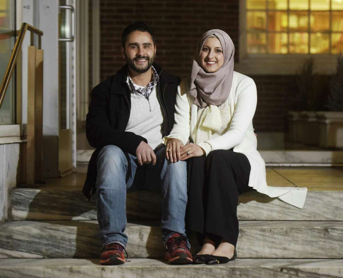 Stamford residents Shaimah Hamdan and her husband Fadi El-Ghussein pose outside the Ferguson Library near their home in downtown Stamford.