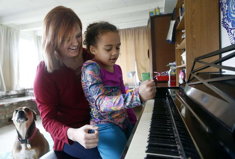 Heather Jacoby plays the piano with her 7-year-old daughter, Billie. Jacoby, who received lifesaving treatment at a Planned Parenthood facility, is upset by efforts to end federal funding for the organization. Photo: Paul Chinn, The Chronicle